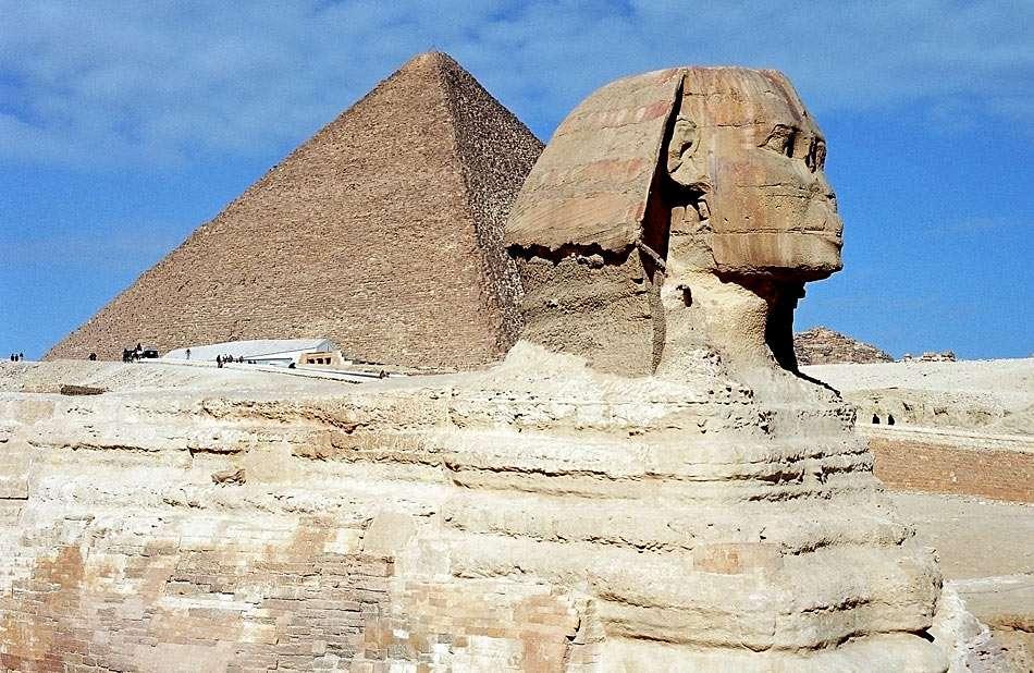 Sfinks na tle piramidy Cheopsa w Egipcie - Pomnik z Doliny Królów w pobliżu Gizy (Egipt) jest najbardziej znanym ze sfinksów. Ciało warującego lwa połączone jest z głową faraona Chefrena. Na drugim planie widać największą z egipsk (10×6)