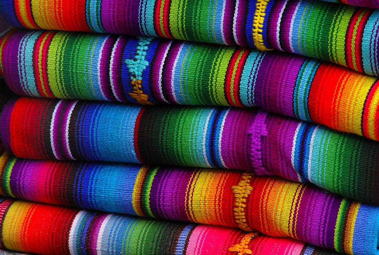 Meksykańskie koce - Koce i długie, bajecznie kolorowe szale, zwane sarape, to ważny element meksykańskiego stroju. Oferowane są na lokalnych targach turystom. Obok sombrera, jest to jedna z najpopularniejszych pamią (19×12)