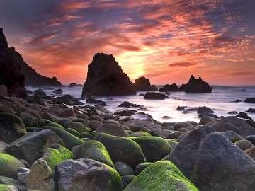 Zachód słońca nad skalistą plażą Ursa (Portugalia)