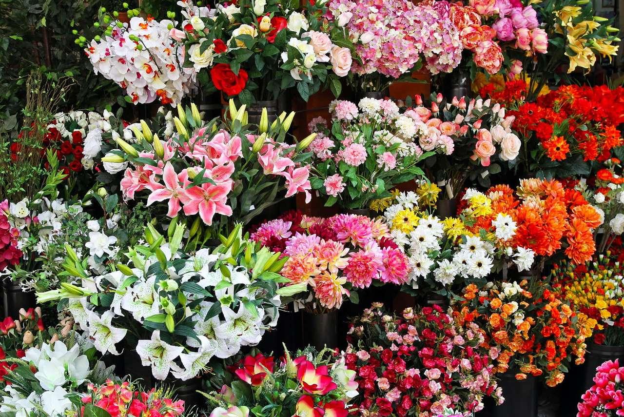 Stoisko ze sztucznymi kwiatami - Dawniej sztuczne kwiaty wyrabiane były z naturalnych materiałów – tkanin i kolorowego papieru lub bibułki. Ze względu na ich trwałość wykorzystywano je przede wszystkim w celu dekorowania re (17×13)