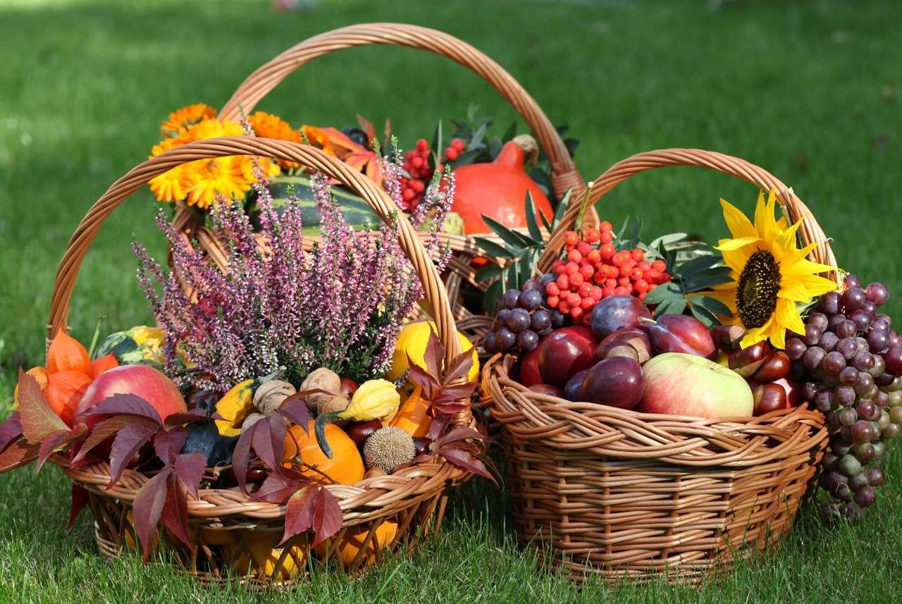 Trzy kosze wiklinowe z jesiennymi owocami i kwiatami