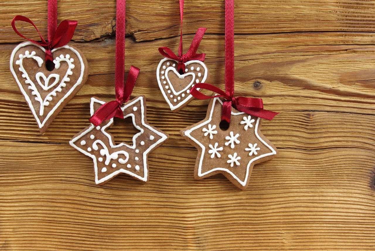 Bożonarodzeniowe pierniki wiszące na czerwonych wstążkach