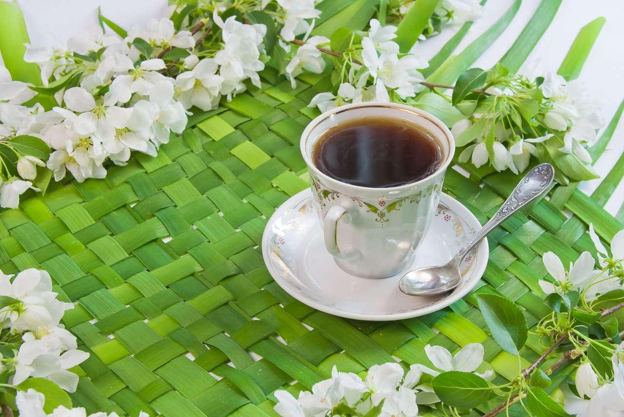 Filiżanka kawy otoczona gałązkami kwitnącej jabłoni - Picie kawy nieodłącznie kojarzy się z przyjemnością. Ma ona bowiem nie tylko działanie pobudzające, ale również uaktywnia neuroprzekaźniki odpowiedzialne za przesyłanie do centralnego ośro (8×6)