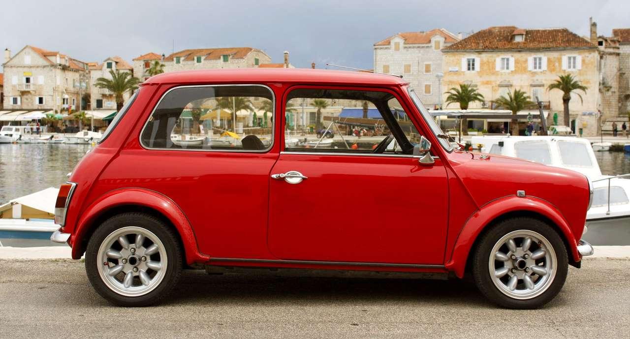 Czerwony samochód Mini 1000 w śródziemnomorskiej wiosce - Mini to niewielkich rozmiarów samochód produkowany przez British Motor Corporation od 1959 do 2000 roku. Auto stało się kultowe w latach 60. XX, a według jury prestiżowego konkursu motoryzacyjne (11×6)