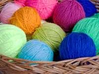Motki kolorowej wełny w wiklinowym koszyku