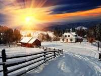 Zachód słońca nad górską wioską zasypaną śniegiem