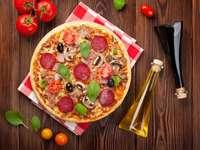 Pizza z salami, bazylią i oliwkami na drewnianym stole