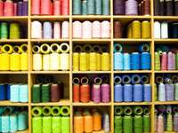 Półki ze szpulami kolorowych nici